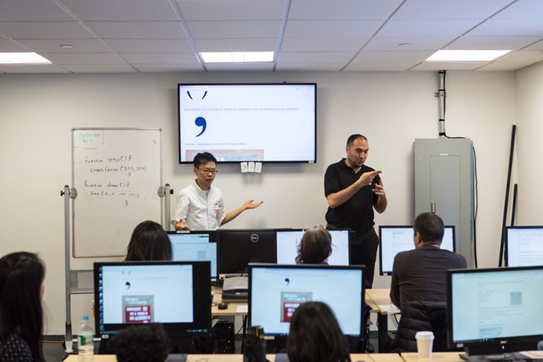 Two volunteers explaining concepts using a white board and a screen to a bunch of deaf and hard of hearing students, each student facing a computer screen.