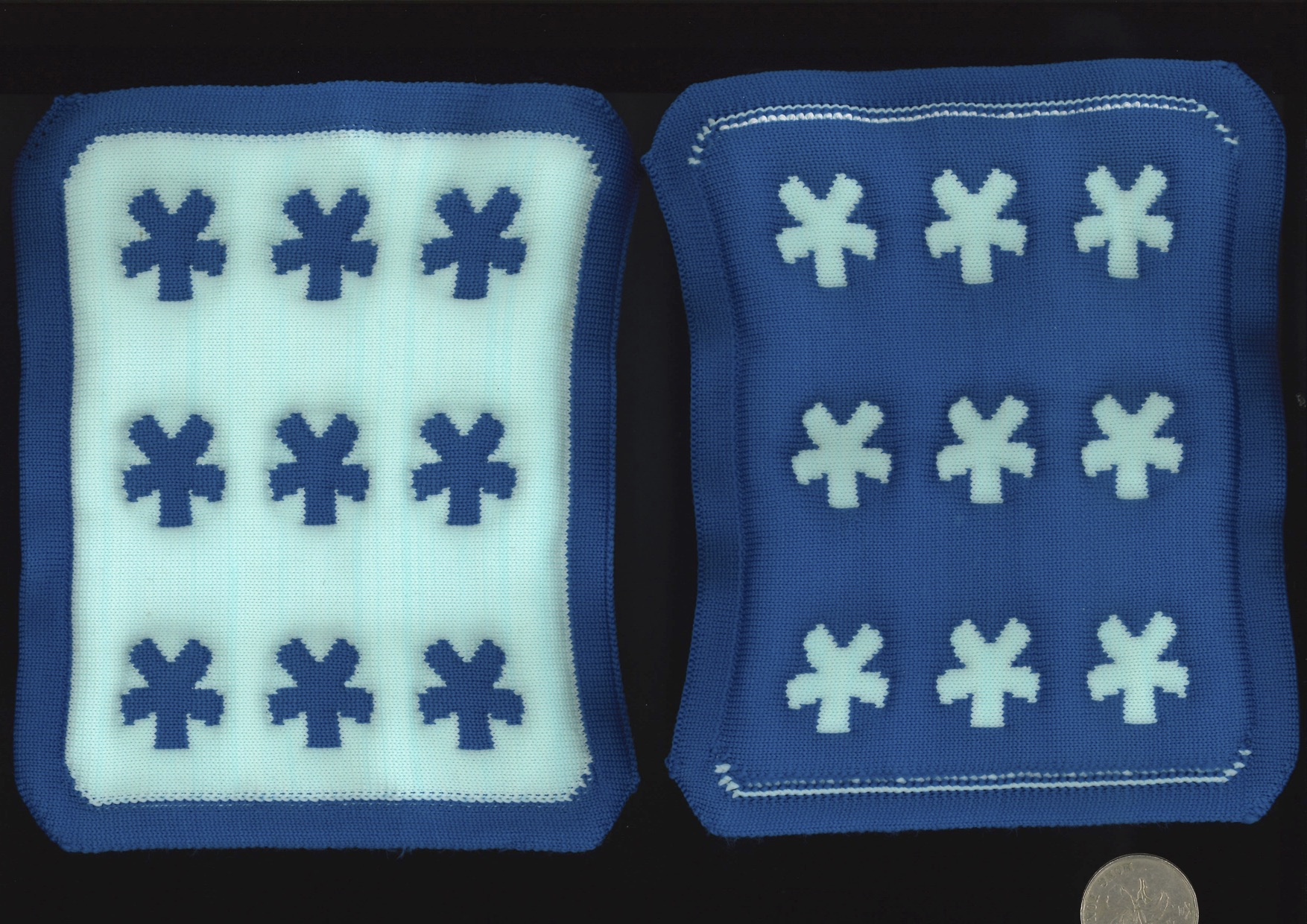 Two sample knit output. It is a knit design of 3 by 3 asterisk stars, with teal and prussian blue alternating with the background and stars. This design uses an embossing technique, so the design pattern can be felt in a tactile manner. The size of the samples are compared to a quarter coin.