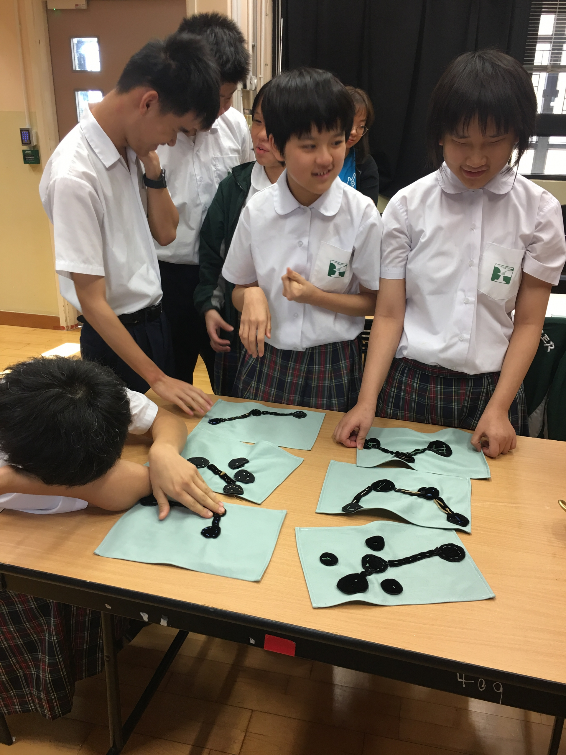 6 students from the Ebenezer School and Home for the Visually Impaired are gathered around a table, touching each other's finished work of hand-sewn black felt and cloth network representations. They are all wearing uniforms from the school. Most of the students look happy and one of the students is crouched on the table.