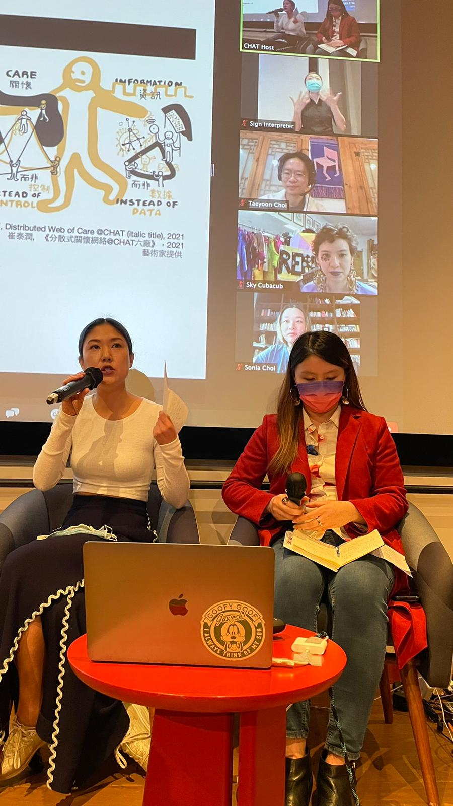 Photo from the Intro Session with Chantal Wong (Eaton HK) and Eugenia Law (CHAT). In the background is a projection of the zoom room, which has a powerpoint and video of a sign interpreter, Taeyoon Choi, Sky Cubacub, and Suhyun Choi.